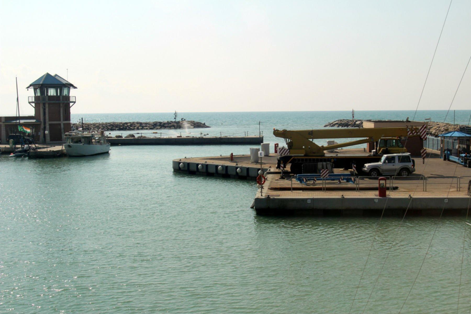 una piattaforma con un'autogru, una macchina e vista del mare e di un faro
