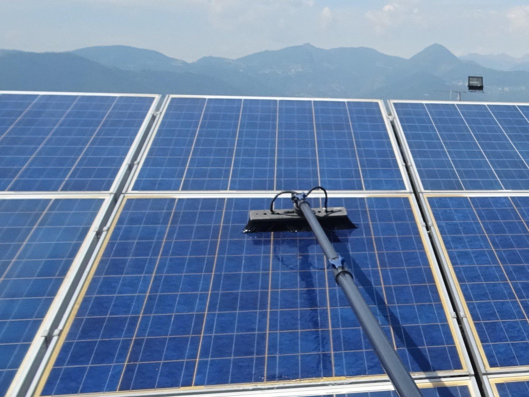 Inquadratura frontale di pannelli fotovoltaici blu su un tetto con spazzola per la pulizia