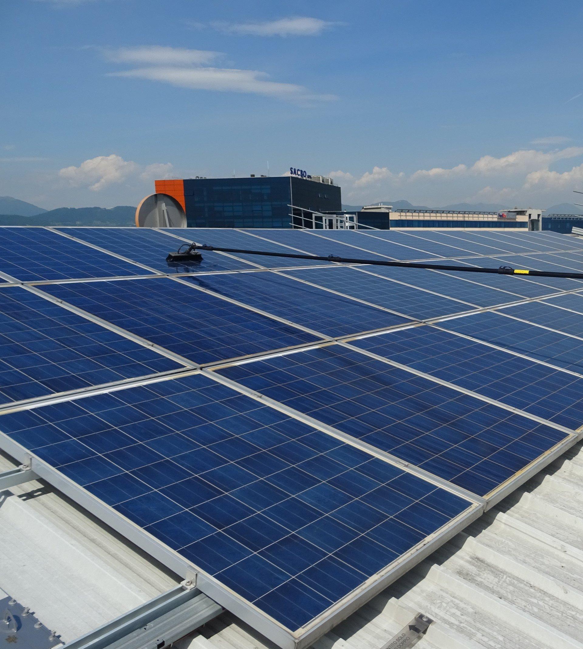 Inquadratura d'angolo di pannelli fotovoltaici blu su un tetto con spazzola per la pulizia