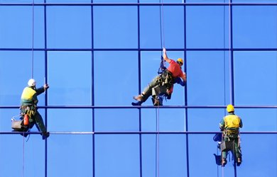 abseiling down a large window installation