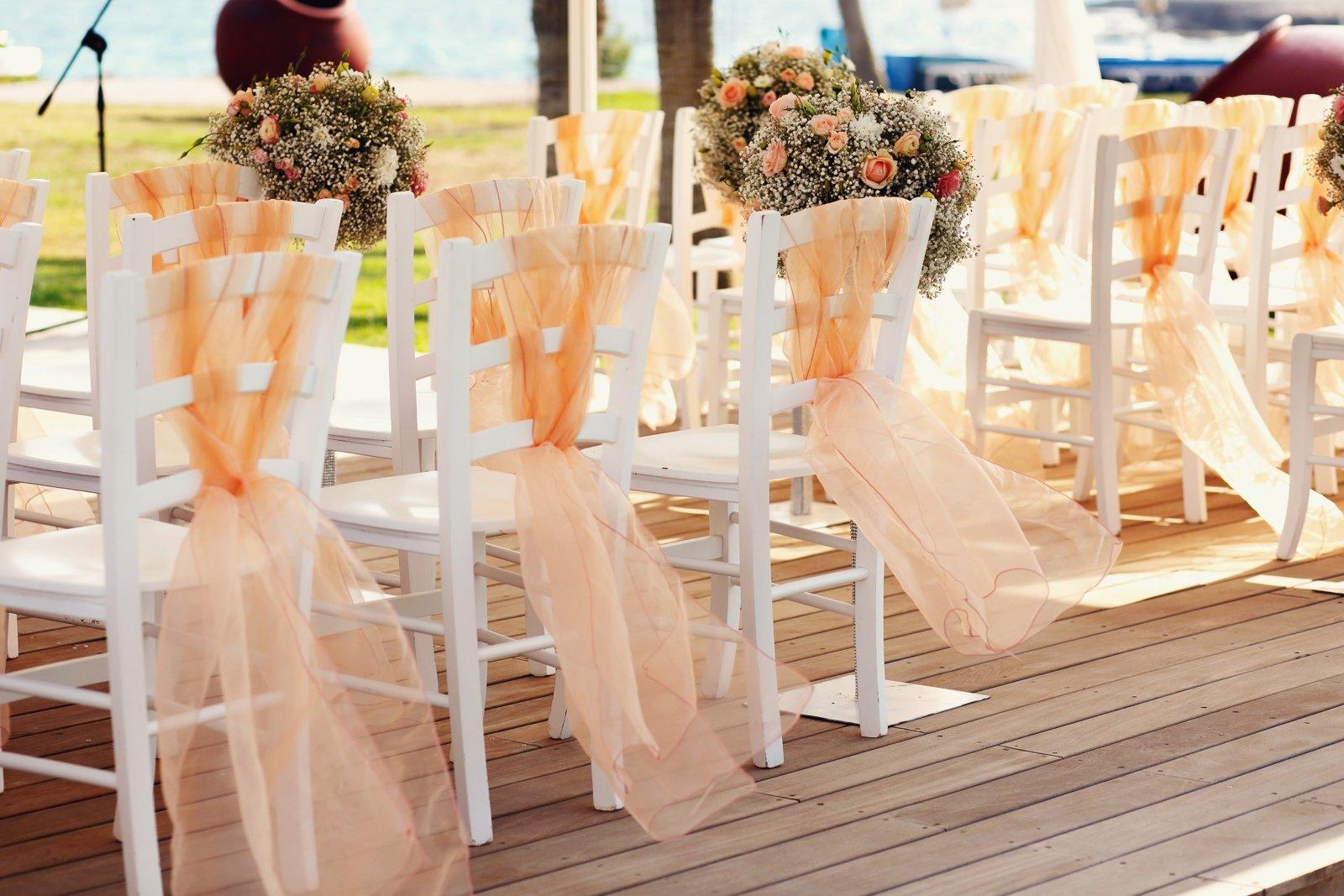 Sedie bianche, legami di tulli arancione, composizioni floreali in bianco e arancio