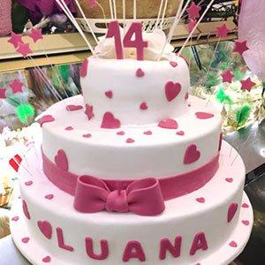 una torta con glassa bianca e fiocchi rosa con scritto Luana