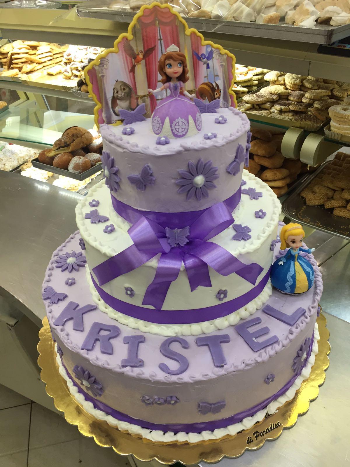 una torta a tre piani bianca con un fiocco viola con scritto Kristel