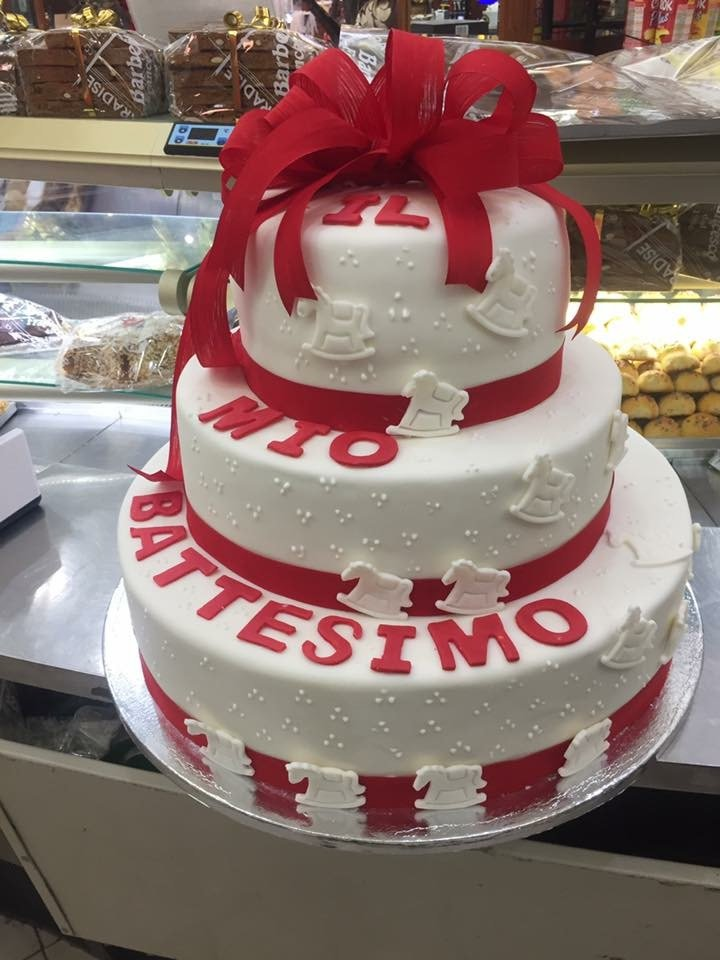 una torta di glassa bianca a tre piani con un fiocco rosso con scritto Mio Battesimo