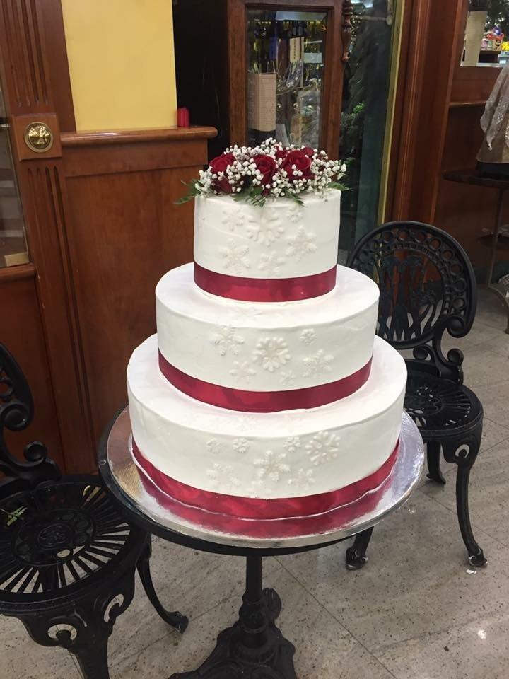 una torta a tre piani di glassa bianca con fiocchi rossi e dei fiori sopra