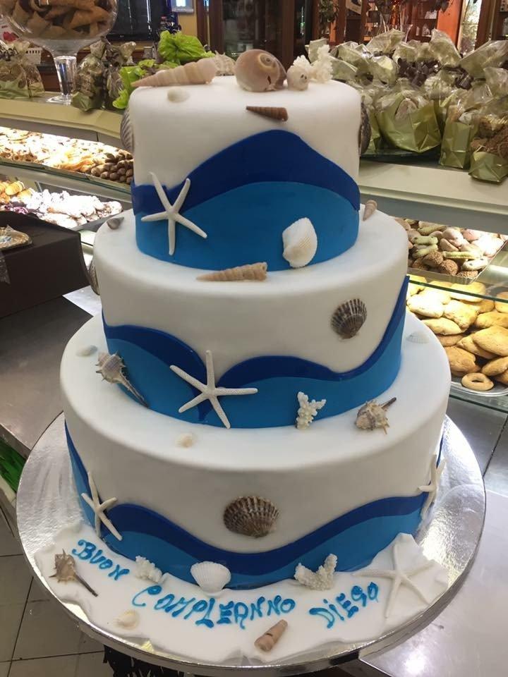 una torta a tre piani di glassa bianca e azzurra con scritto Buon Compleanno Diego