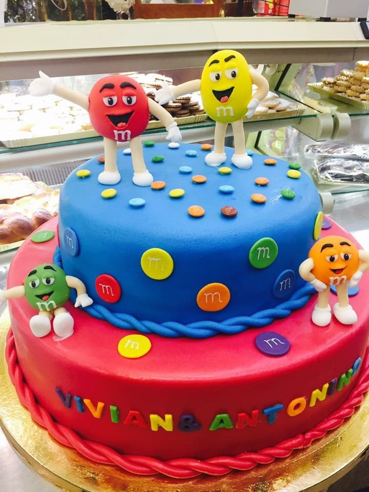una torta a due piani rossa e blu con i personaggi delle M&M's