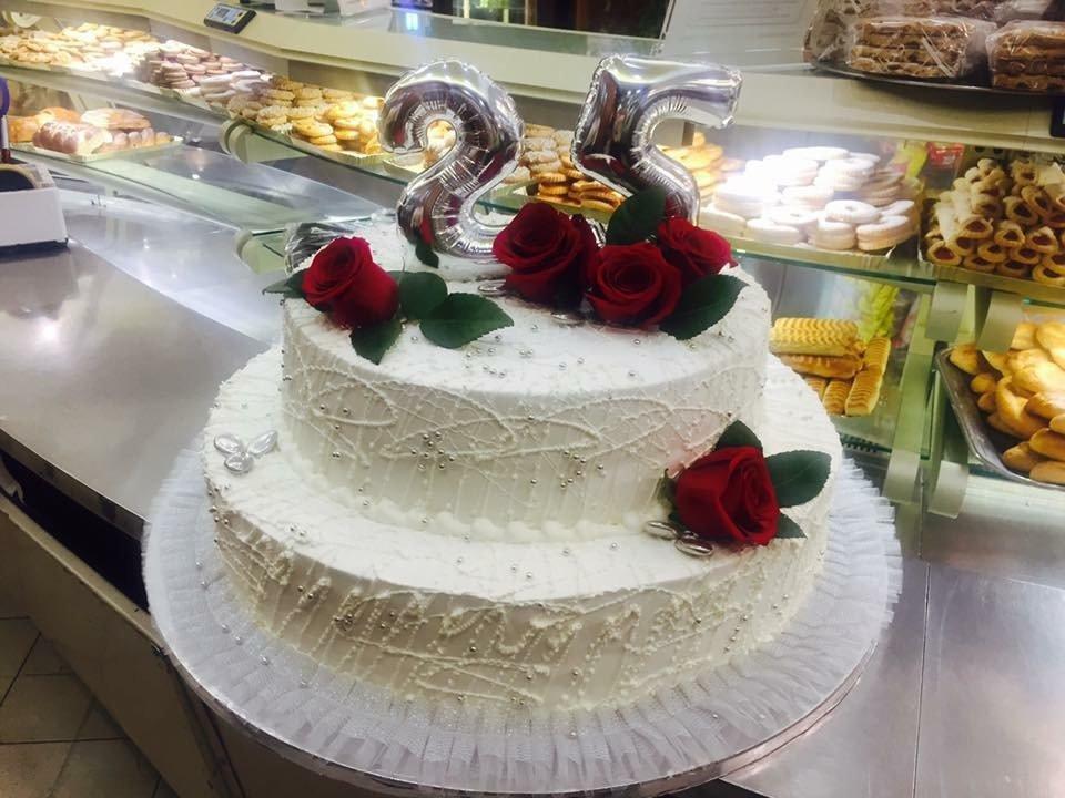 una torta di panna bianca a due piani con delle rose rosse e il numero 25