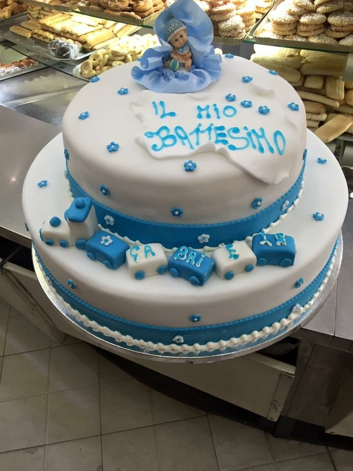 una torta di glassa bianca e azzurra con scritto il Mio Battesimo e un pupazzetto sopra