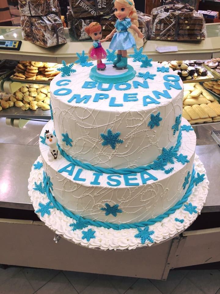 una torta a due piani di panna bianca e azzurra con  delle stelle e la scritta buon compleanno Alisea