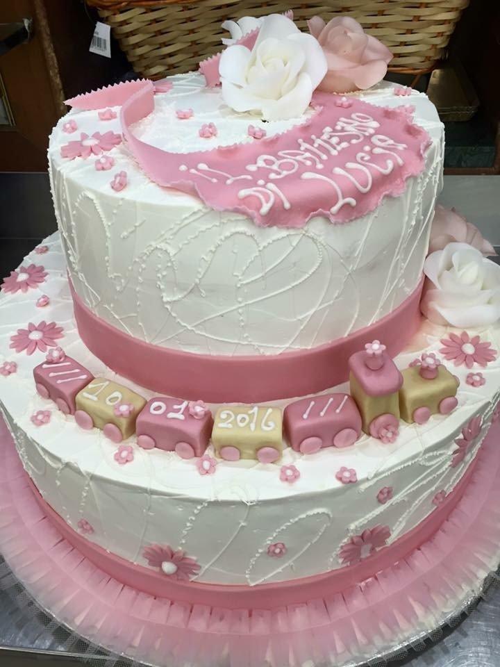 una torta a due piani di glassa bianca e rosa con scritto Il Battesimo Luca