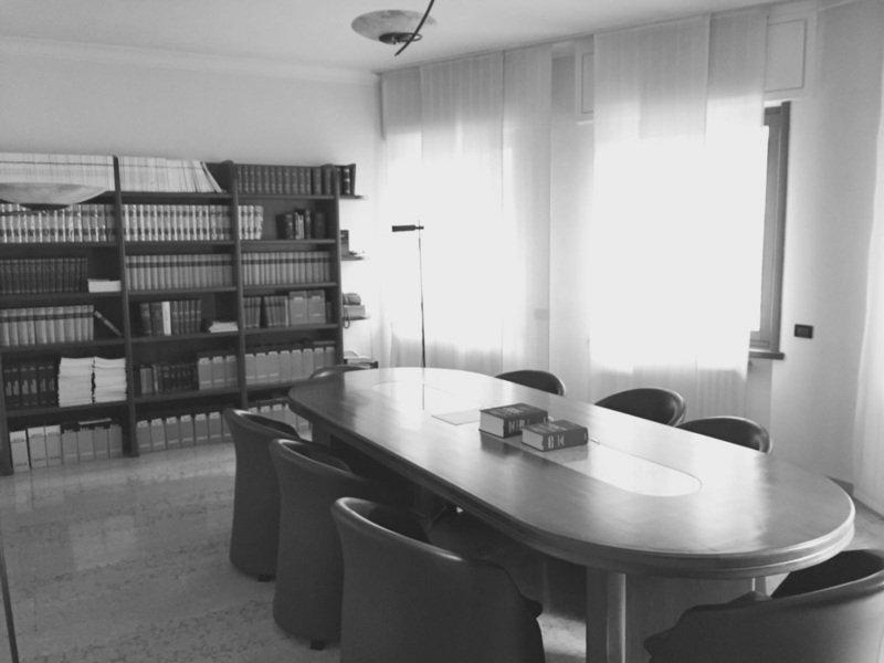 Foto in bianco e nero di un ufficio di consulenza legale, libreria con vecchi libri di leggi,sobrio,con molta luce naturale