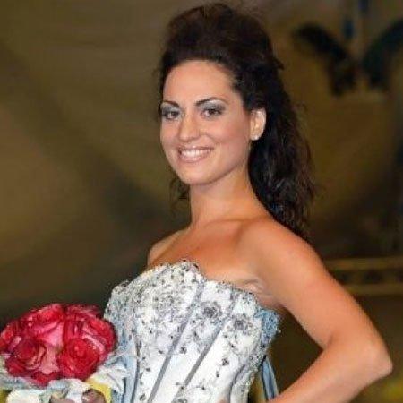 una donna con capelli neri con in mano un bouquet di fiori