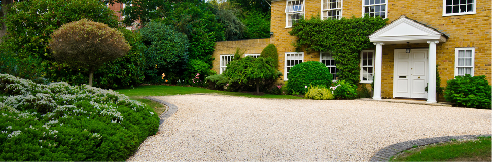 large gravel driveway leading to a house