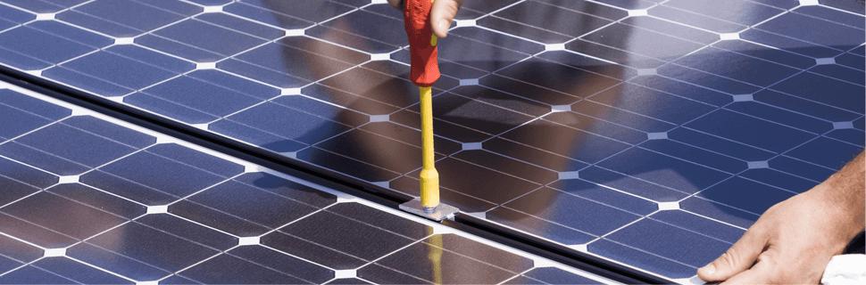 man repairing solar panels