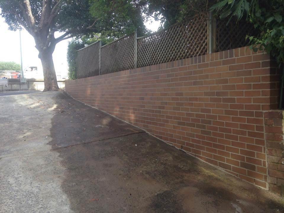 sidewalk next to brick wall