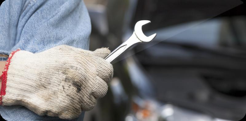 una mano con un guanto da lavoro grigio e con in mano una chiave inglese
