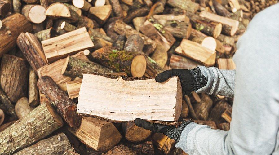 una persona prende un tronco da un mucchio di legna