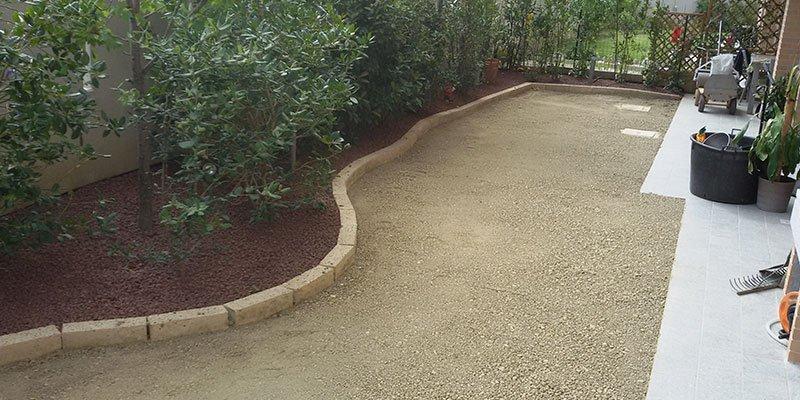 un cortile di una casa con sulla sinistra un aiuola con delle piante