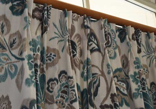brown and teal curtain with wood rod