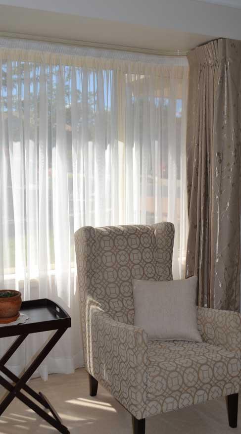 white shear curtain near chair
