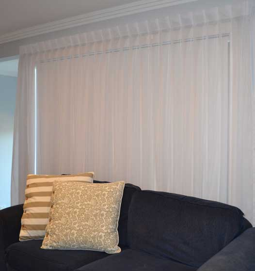 thick white curtain behind bed