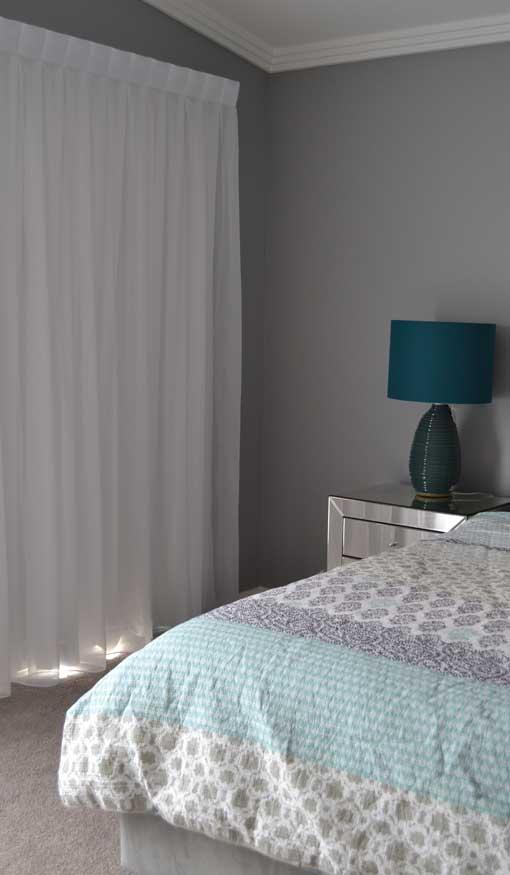 blue lamp near grey wall