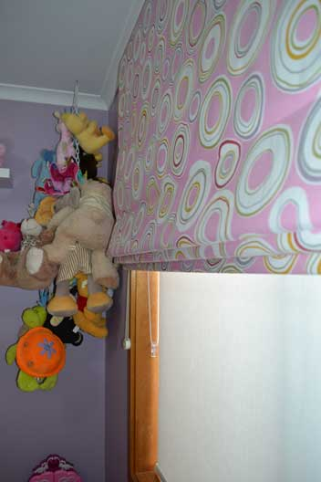 stuffed animals hanging by pink curtains
