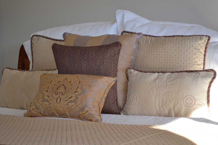 golden pillows on bed