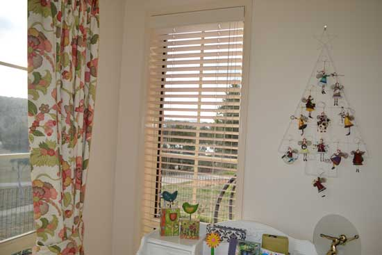 cream blinds with colorful bird decorations in front