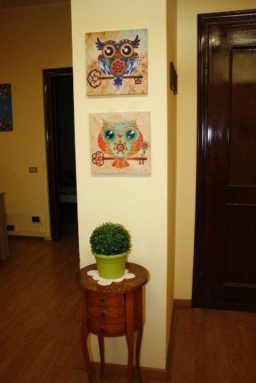 un tavolino con sopra una pianta e due quadretti a muro raffiguranti dei gufi