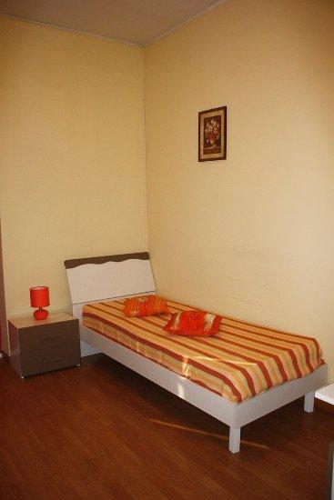 una camera con un letto singolo e un comodino