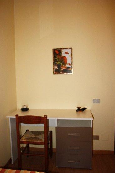 una scrivania con dei cassetti, una sedia e un quadro a muro