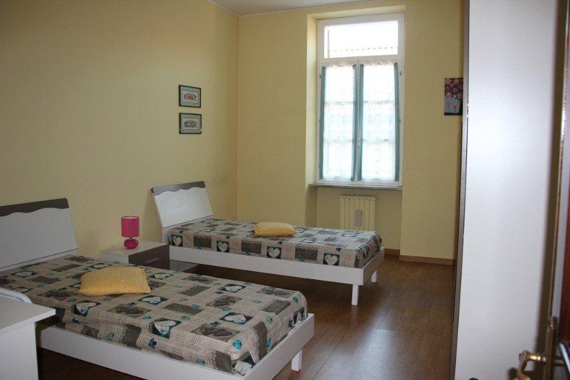 una stanza con due letti singoli, un comodino,un quadretto e vista della finestra