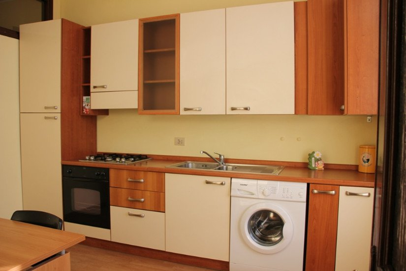 dei mobili di una cucina in legno bianco e marrone e una lavatrice a incastro