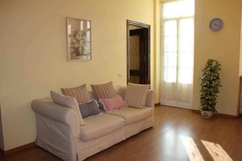un salotto con un divano beige con dei cuscini,un quadro al muro e un vaso con una pianta