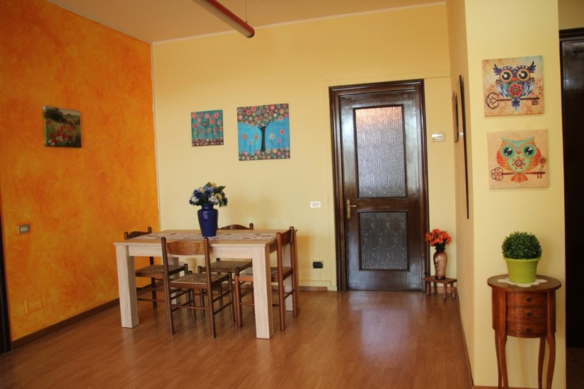 una sala da pranzo con un tavolo con sopra un vaso di fiori, le sedie e sulla destra un tavolino con sopra una pianta e dei quadretti raffiguranti dei gufi
