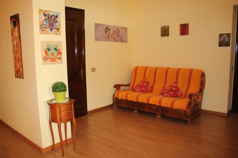 un divano giallo a righe rosse, una porta, quadri sul muro e un tavolino con sopra un vaso con una pianta
