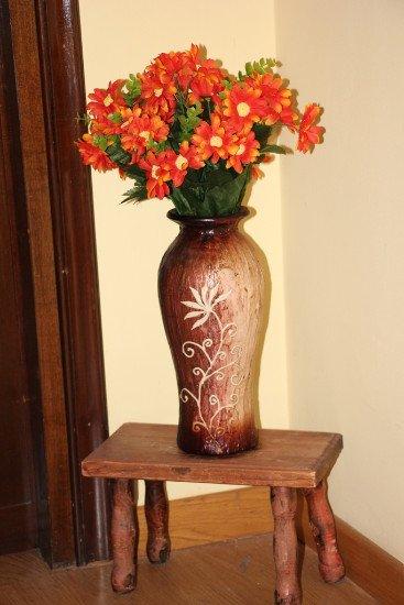 un tavolino con sopra un vaso di fiori rossi