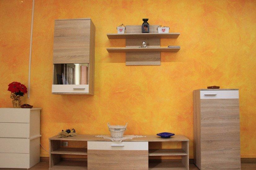 un mobile tv color beige, delle mensole e una cassettiera con sopra un vaso di fiori