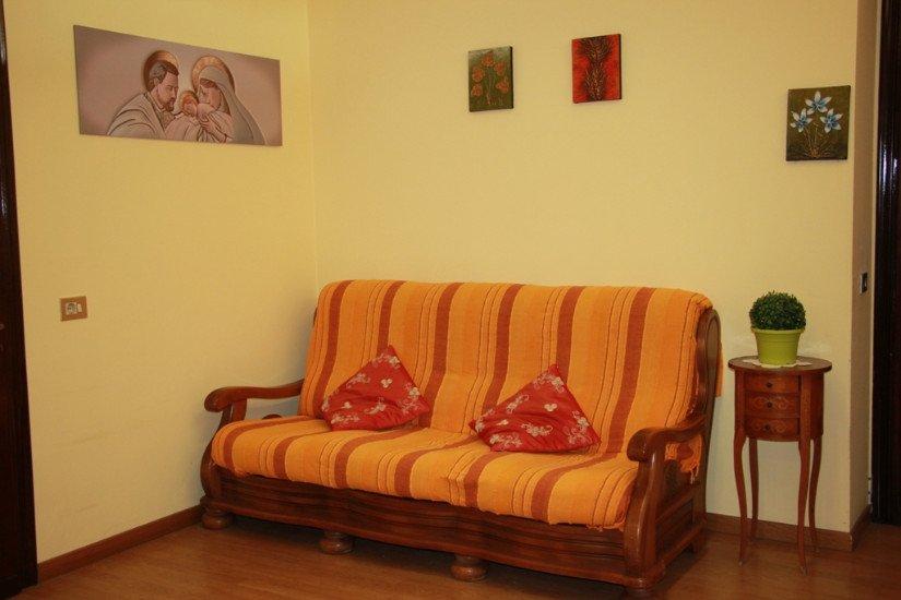 un divano arancione a righe rosse, un tavolino con sopra un vaso con una pianta e dei quadri al muro