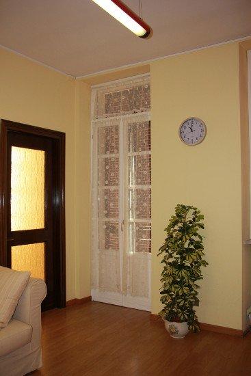 vista di una finestra con delle tende bianche, un vaso con una pianta e un orologio a muro