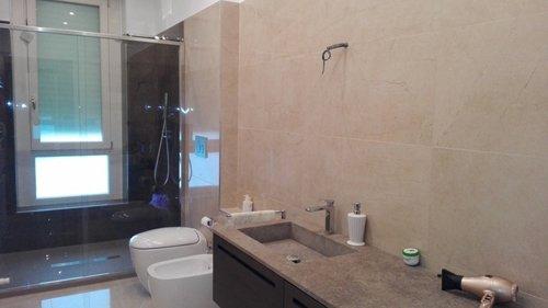 vista interna di bagno con lavabo e bidè con prodotti cosmetici