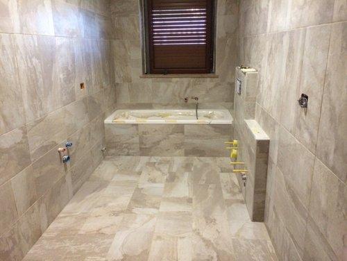 bagno con parete e pavimento in marmo e persiana