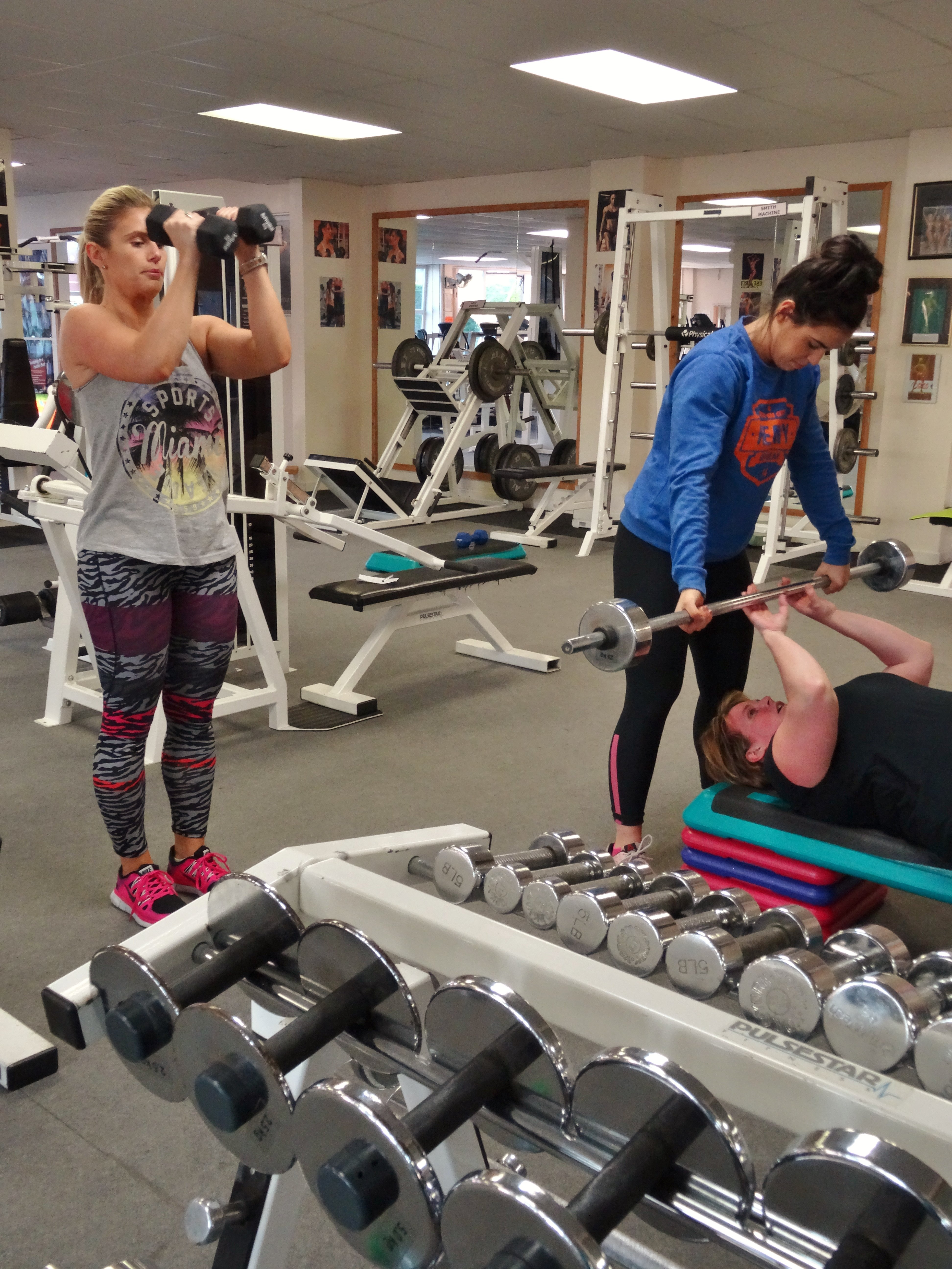 certified trainer assisting people at the gym
