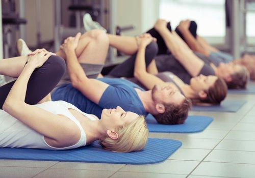 persone che fanno stretching su un tappetino