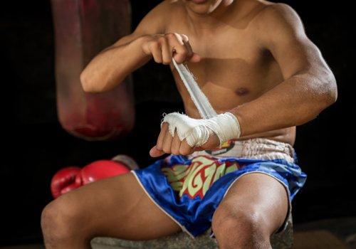 un uomo vestito da THAI BOXE  mentre  si mette una benda nella mano