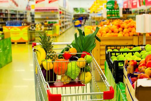 carrello con frutta e verdura in mezzo a un corridoio di un supermercato