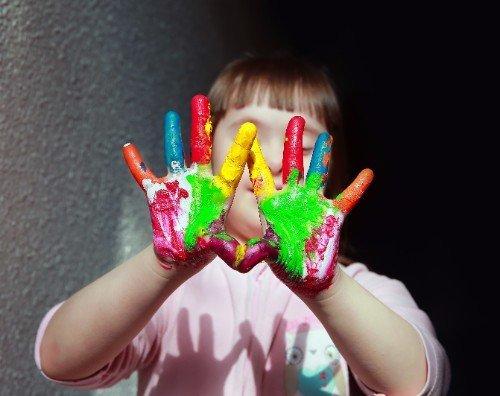 bimba con mani sporche di pittura