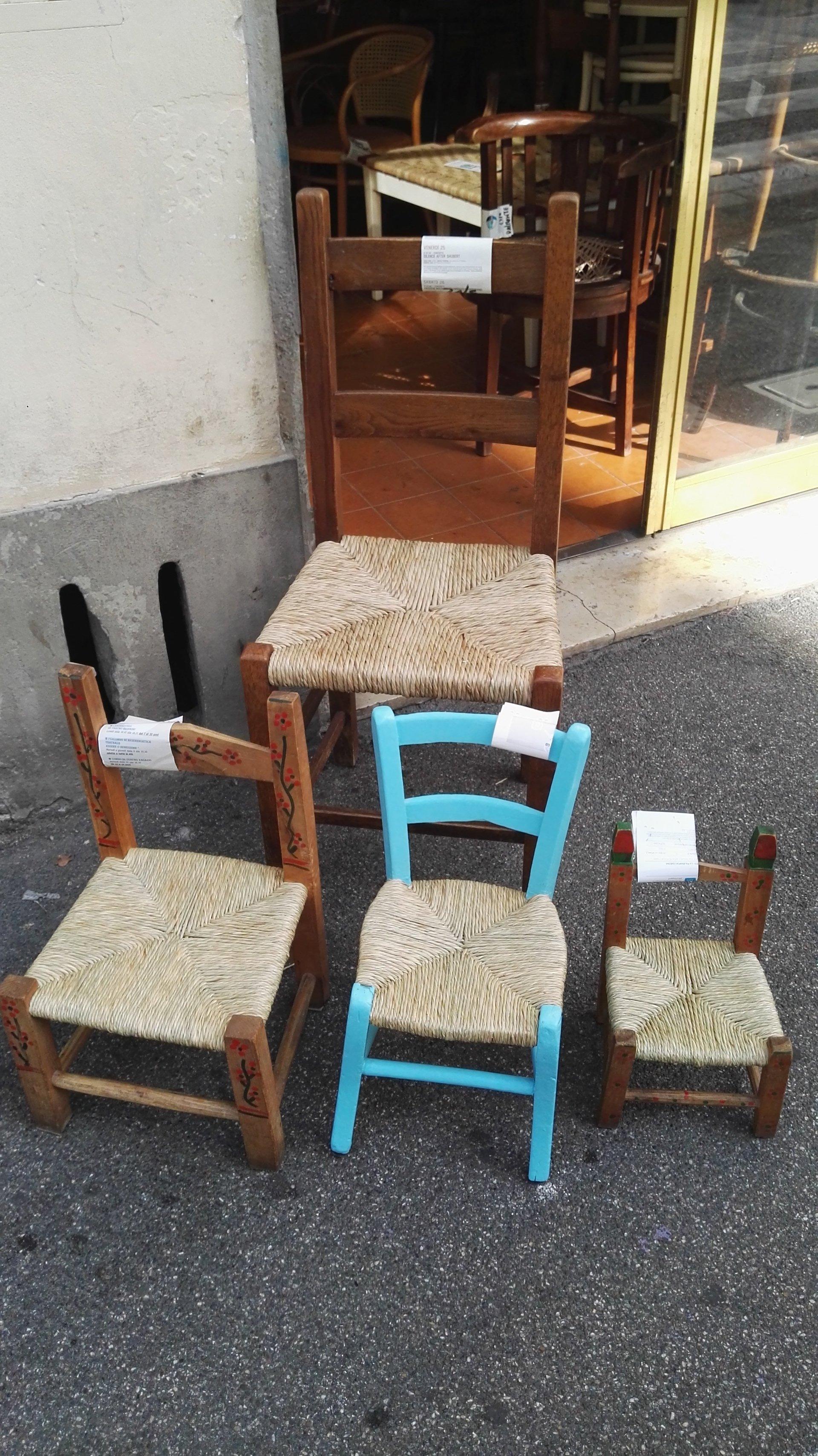 vista di sedie capovolte con sedute di paglia intrecciata a mano